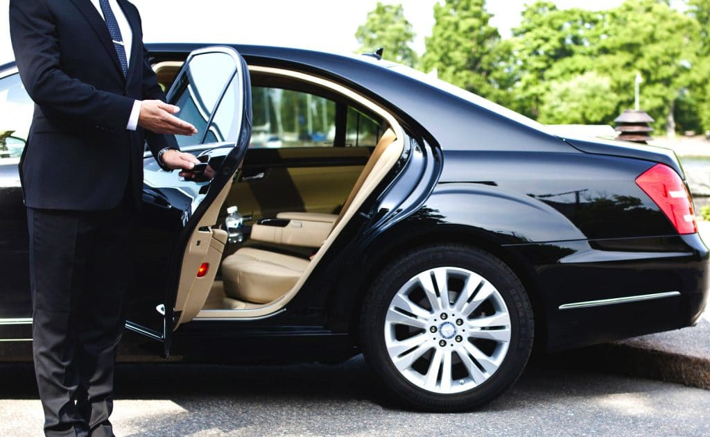 Chauffeur opening door of a luxury car