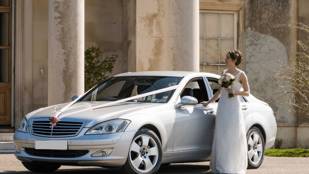 Bride standing by a luxury car